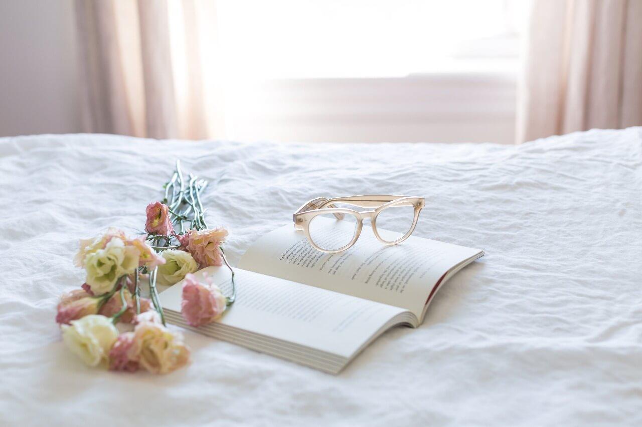 Livro aberto com um buquê de flores e um óculos